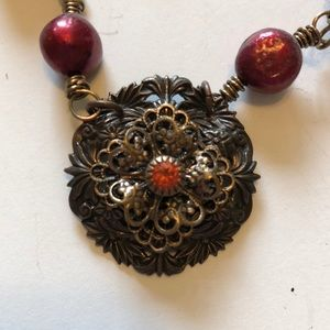 Artisan necklace with red accents.